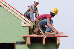 Hispanic carpenters preparing trim roof panel Stock Photo