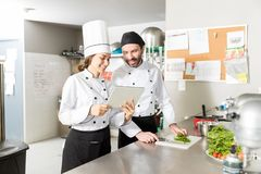 Hispanic Chefs Using Digital Tablet In Kitchen. Female chef smiling while sharing tablet computer with colleague in kitchen royalty free stock images