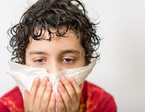 Hispanic child blowing his nose. Boy with a runny nose. Dust allergy. Kid suffering from a cold. Hispanic child with curly hair suffering from the flu. Kid Stock Image