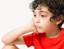 Hispanic Child Expressions of sadness, wondering and dispair. Boy with curly hair making different mood expressions. White backgro. Latin boy with red T-shirt Royalty Free Stock Photos