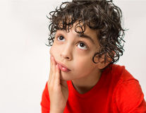 Hispanic Child Expressions of sadness, wondering and dispair. Boy with curly hair making different mood expressions. White backgro. Sad Hispanic boy wondering Stock Images
