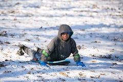 Hispanic Child Having Fun Sledding on the Snow Royalty Free Stock Image
