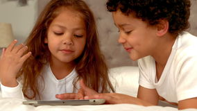 Hispanic children playing together on a tablet. At home stock video