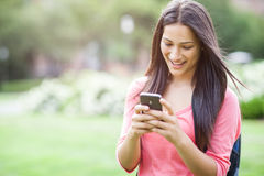 Hispanic college student texting. A beautiful hispanic college student texting on her cellphone Royalty Free Stock Images
