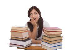 Hispanic college student woman with stack of books. Bored High school or college Latina female student sitting by the desk with pile of books in front of her Stock Image