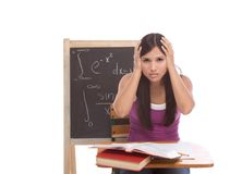 Hispanic college student woman studying math exam. Stressed High school or college Latina female student sitting by the desk at math class. Blackboard with Stock Image