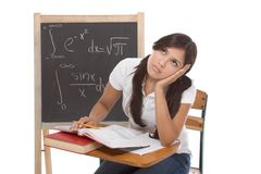 Hispanic college student woman studying math exam. Stressed High school or college Latina female student sitting by the desk at math class. Blackboard with Royalty Free Stock Image