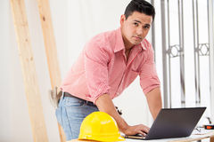 Hispanic contractor at work. Good-looking Hispanic contractor doing some work on a laptop on site Stock Images