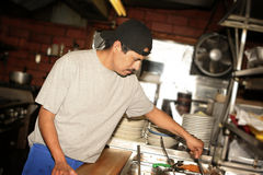 Hispanic Cook. Hispanic kitchen staff. Grid spot used on flash to place emphasis on subject Stock Photos