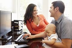 Hispanic couple and baby in home office Royalty Free Stock Photos
