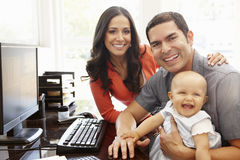 Hispanic couple and baby in home office Stock Image