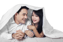 Hispanic couple on bed under blanket Stock Photo