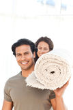 Hispanic couple carrying a carpet standing Royalty Free Stock Photo