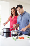 Hispanic Couple Cooking Meal At Home Stock Image