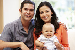 Hispanic couple at home with baby Stock Image
