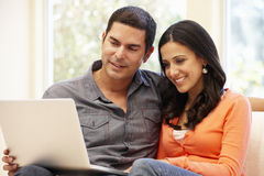 Hispanic couple at home with laptop Stock Photos