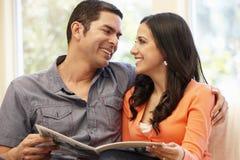 Hispanic couple at home reading magazine Stock Photography