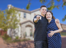 Hispanic Couple with House Keys In Front of New Home. Happy Hispanic Couple In Front of New Home Showing Off Their House Keys stock photography