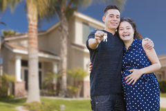 Hispanic Couple with House Keys In Front of New Home Stock Photos