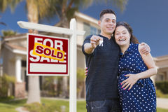 Hispanic Couple, Keys, New Home and Sold Real Estate Sign. Young Happy Pregnant Hispanic Young Couple with House Keys in Front of Their New Home and Sold For royalty free stock photos