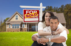 Hispanic Couple New Home and Sold Real Estate Sign Stock Photo