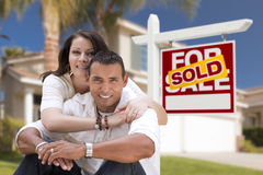 Hispanic Couple, New Home and Sold Real Estate Sign. Young Happy Hispanic Young Couple in Front of Their New Home and Sold For Sale Real Estate Sign royalty free stock photography