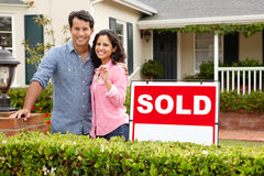 Hispanic couple outside home with sold sign. Hispanic couple standing outside home with sold sign smiling at camera Royalty Free Stock Photos