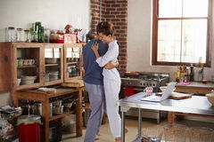Hispanic couple in pyjamas embracing in kitchen Royalty Free Stock Images