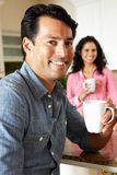 Hispanic couple relaxing in kitchen Royalty Free Stock Photo