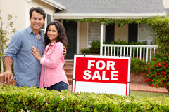 Hispanic couple satnding with a sign outside house. Smiling Royalty Free Stock Image