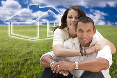 Hispanic Couple Sitting in Grass Field with Ghosted House Behind Royalty Free Stock Images