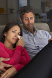 Hispanic Couple On Sofa Watching Sad Movie On TV Royalty Free Stock Image