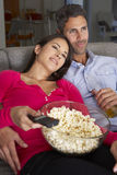 Hispanic Couple On Sofa Watching TV And Eating Popcorn Stock Photo