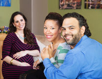Hispanic Couple with Surrogate Mother. Smiling Hispanic couple sitting with beautiful surrogate mother Royalty Free Stock Photo