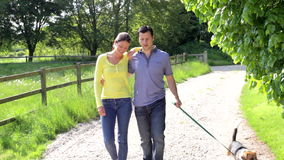 Hispanic Couple Taking Dog For Walk In Countryside