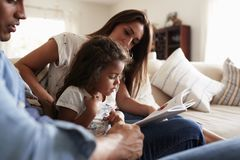Hispanic couple and their young daughter sitting on the sofa reading a book together at home royalty free stock photo