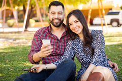 Hispanic couple using smartphones Stock Photography