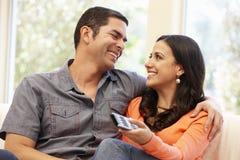 Hispanic couple watching television Stock Photography