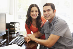 Hispanic couple working in home office Stock Images