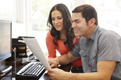 Hispanic couple working in home office Stock Photo