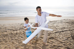 Hispanic dad, girl playing with toy plane on beach Stock Images