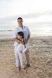 Hispanic dad and girl standing together on beach Stock Photos
