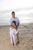 Hispanic dad and girl standing together on beach Royalty Free Stock Photography