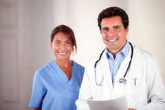 Hispanic doctor couple looking and smiling at you Stock Photo