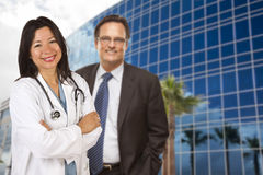 Hispanic Doctor or Nurse and Businessman in Front of Building. Attractive Hispanic Doctor or Nurse and Businessman in Front of Corporate Building royalty free stock images