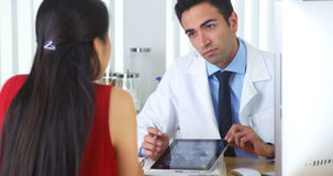 Hispanic doctor reviewing brain xrays on tablet with patient Stock Photos