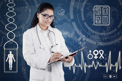 Hispanic doctor with stethoscope and holds clipboard Stock Photo