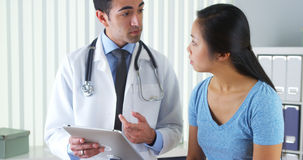 Hispanic doctor talking with patient with test results on tablet Royalty Free Stock Photography