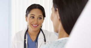 Hispanic doctor talking to female patient Royalty Free Stock Photo