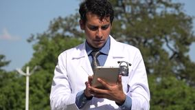 Hispanic doctor using tablet. A handsome adult hispanic man stock video